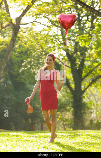 Woman with red heart shape balloon walking in park - Stock Image