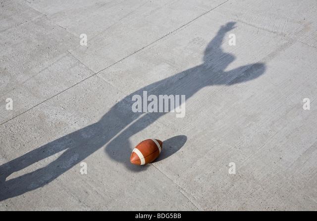 Shadow throwing an American football - Stock Image
