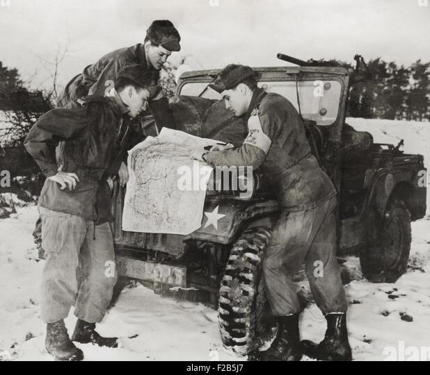 Elvis Presley and other soldiers read a map on maneuvers in Germany. He served with the with 1st Medium Tank Battalion, - Stock Image