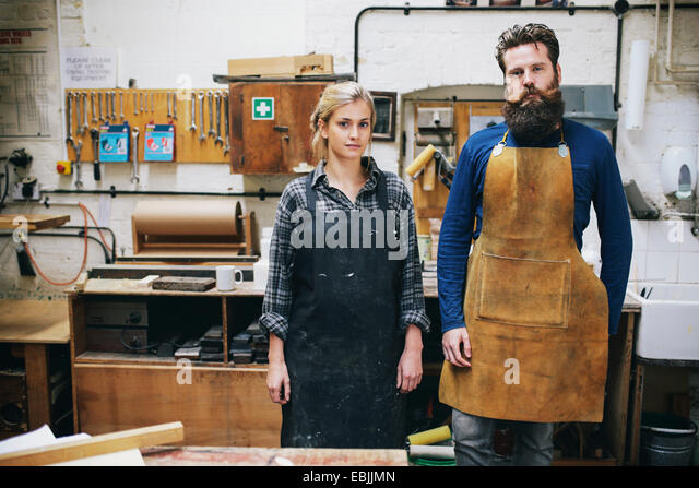Portrait of craftsman and woman in organ workshop - Stock Image