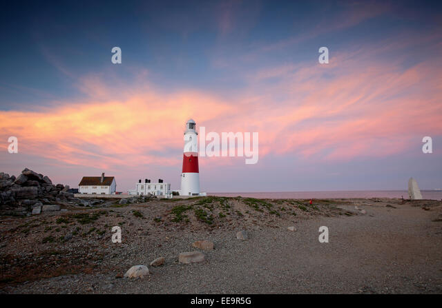 The large lighthouse at Portland Bill in Weymouth Dorset stands on the rocks during sunset - Stock Image