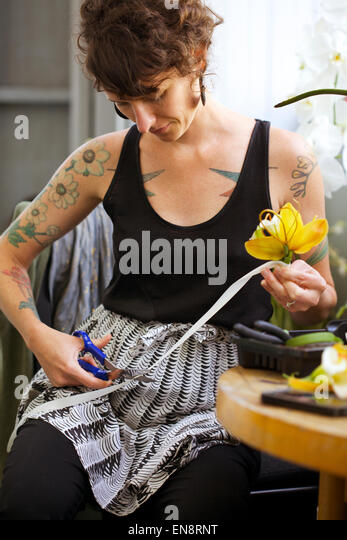 A tattooed woman florist cuts the white ribbon on a boutonniere made of a yellow orchid with a pair of blue handled - Stock Image