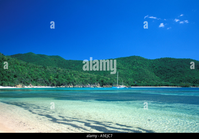 St John US Virgin Islands National Park Reef Bay South Shore Beach water and sailboat - Stock Image