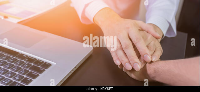 doctor's hands holding  patient's hand for encouragement and empathy - Stock Image