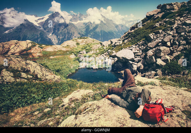 Traveler Man laying relaxing with backpack Travel Lifestyle concept serene view mountains landscape on background - Stock Image