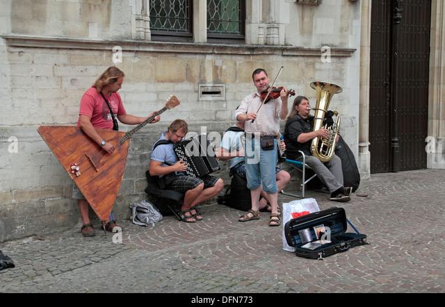 Street musicians, including the amazing looking balalaika, in historic Bruges (Brugge), West Flanders, Belgium. - Stock Image
