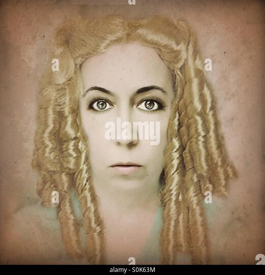 Woman looking straight ahead with golden curls - Stock Image