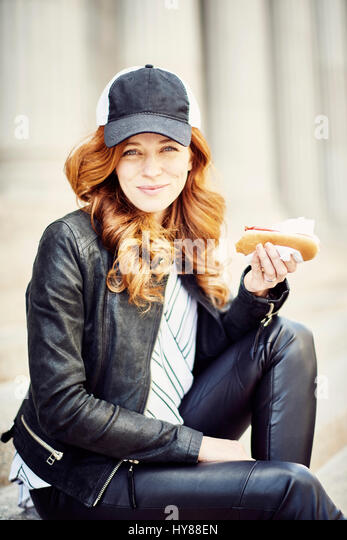 Young women in baseball cap eating a hot dog on the steps of the New York post office - Stock Image