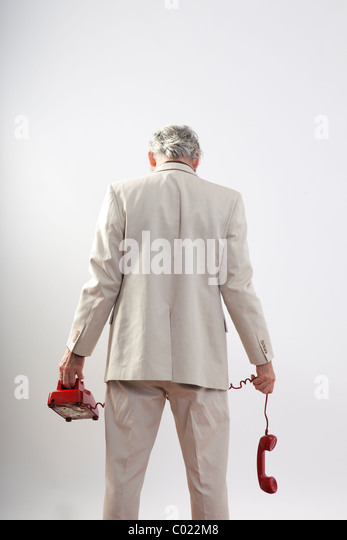 man's back to us hold red phone dangling in defeat - Stock Image