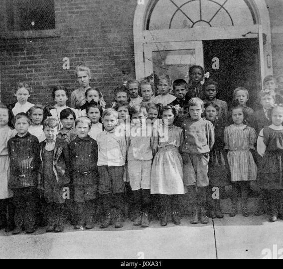 Full length landscape shot of schoolchildren, standing, some African American, 1915. - Stock Image