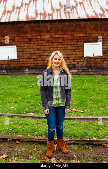 Lifestyle portrait of a woman outdoors with a barn in the background. - Stock-Bilder