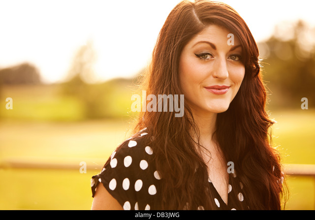 Woman standing in country setting with sun at her back - Stock Image