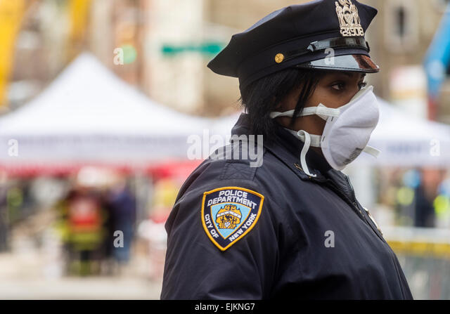 New York, NY - 28 March 2014 A woman police officer wearing a respirator during the recovery of the 26 March gas - Stock Image