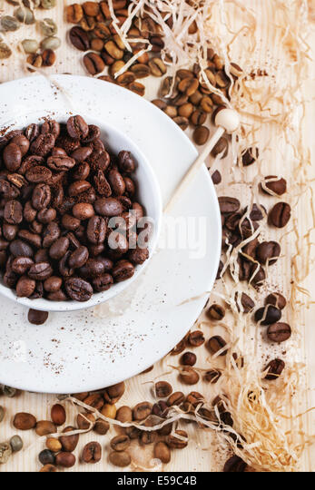 Green and brown decaf unroasted coffee beans and cup of roasted coffee beans on wooden table with chips. Top view. - Stock Image