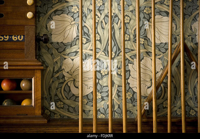 Detail of part of the Billiard Room with cues lined up against the William Morris Pimpernel wallpaper, and part - Stock-Bilder