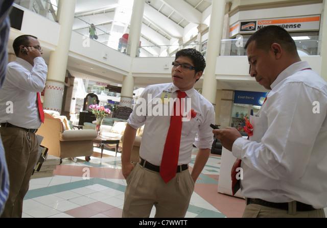 Managua Nicaragua Metrocentro shopping center centre mall business atrium Hispanic man group sales clerk uniform - Stock Image