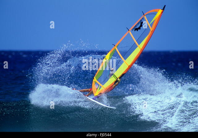 Almost skating over the wave a windsurfer performs with  bright yellow sail on blue Pacific sea at Hookipa, Hawaii, - Stock-Bilder
