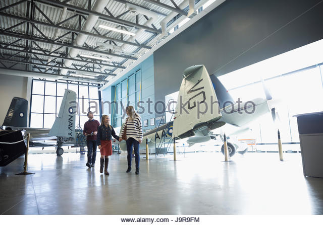 Family holding hands, walking among propellor airplanes in war museum - Stock-Bilder
