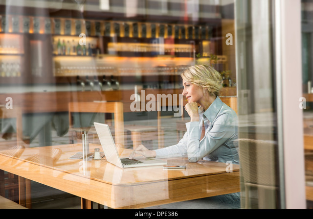 Businesswoman using laptop, view through window - Stock-Bilder