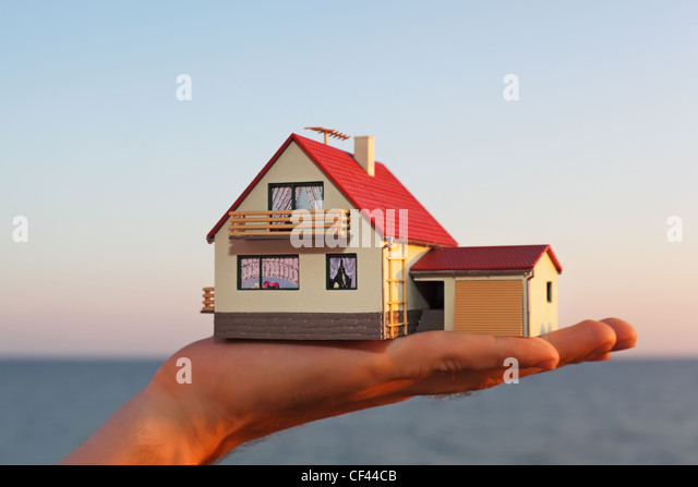 model of house with garage on hand against sea - Stock Image