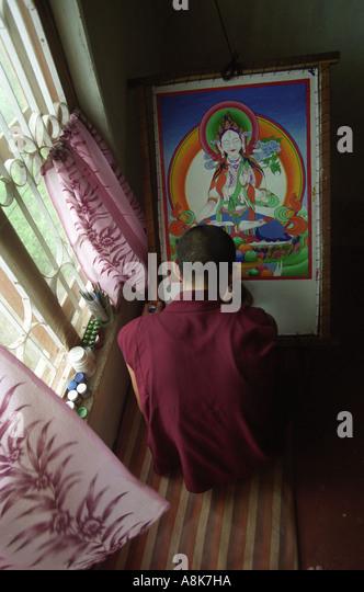 A Tibetan Monk works on a traditional Tibetan painting of the White Tara deity. - Stock-Bilder