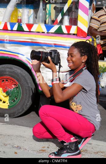 Miami Florida Little Haiti Caribbean Market Place Carnival marketplace community event Black girl teen photographer - Stock Image