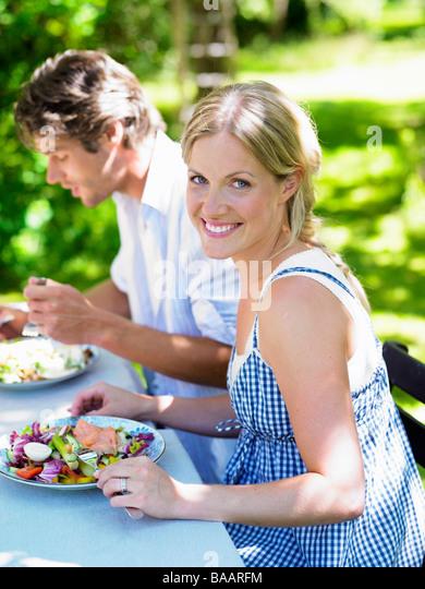 Couple having dinner in the garden, Stockholm, Sweden. - Stock-Bilder