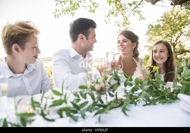 A bride and groom sitting at the top table with their friends at an outside wedding - Stock Image