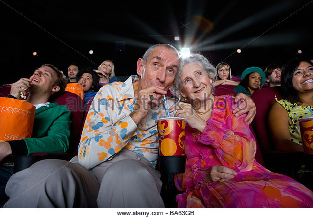 Senior couple sharing drink in cinema, low angle view - Stock-Bilder