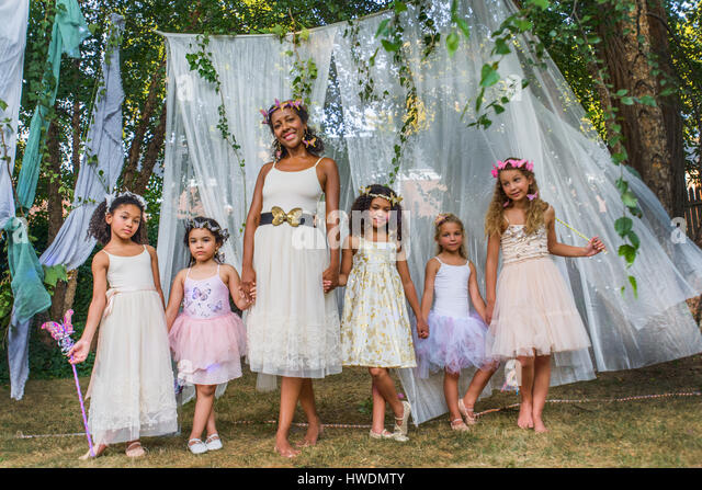 Portrait of mature woman with group of young girls, dressed as fairies, outdoors - Stock-Bilder