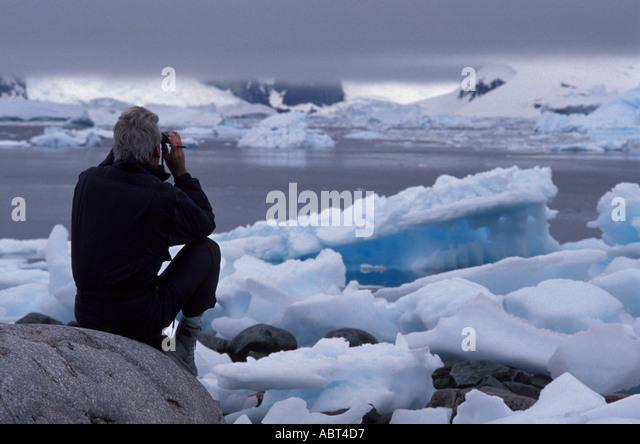 ANTARCTICA Man Scans Horizon with Binoculars icebergs - Stock Image