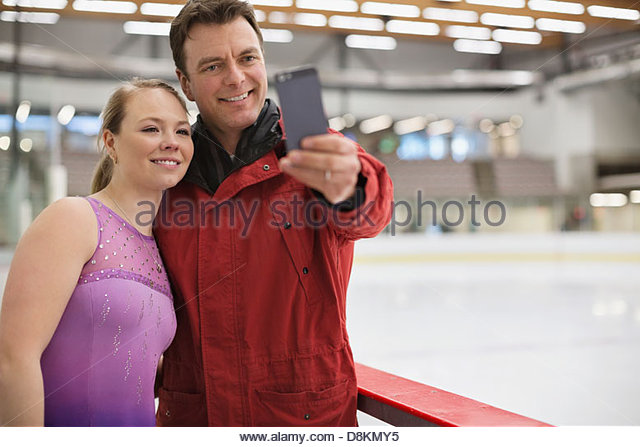 Coach and figure skater taking photograph in skating rink - Stock Image
