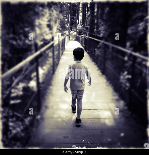 A six year old boy walks across a foot bridge by himself. - Stock Image