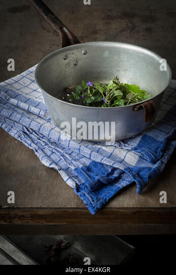 Wild herbs in vintage colander on wooden table - Stock Image