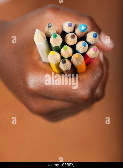 Childs hand gripping colored pencils, Johannesburg, Gauteng Province, South Africa - Stock Image