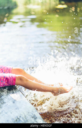 Low section of girl (8-9) splashing water with legs - Stock Image