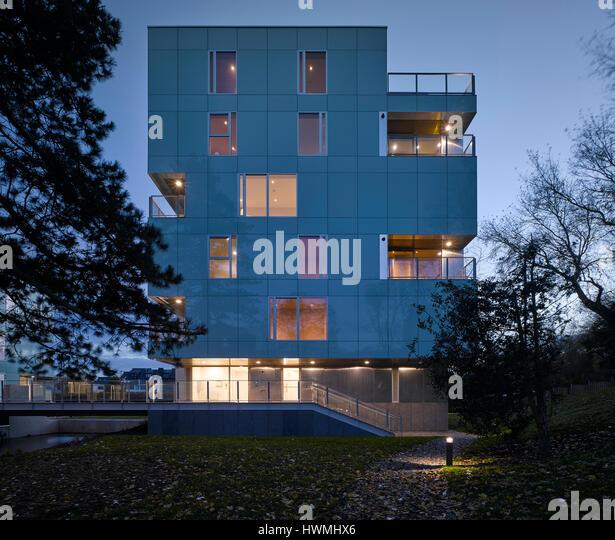 Dusk view of exterior showing stairway and lit interior. Dunluce Apartments, Ballsbridge, Ireland. Architect: Derek - Stock-Bilder