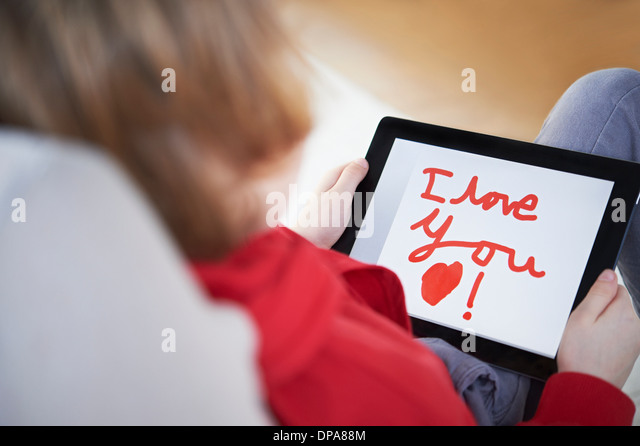 Rear view of boy holding tablet saying 'I love you' - Stock Image