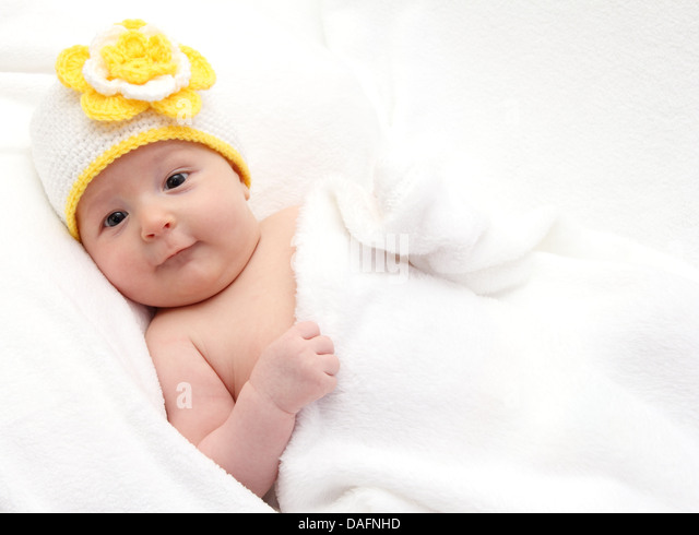 Baby with a knitted white hat baby on back - Stock Image