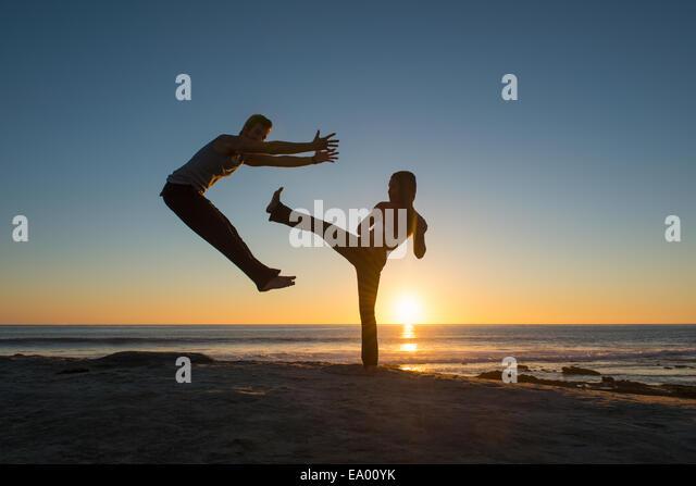 People in jumping and kicking poses on Windansea beach, La Jolla, California - Stock Image