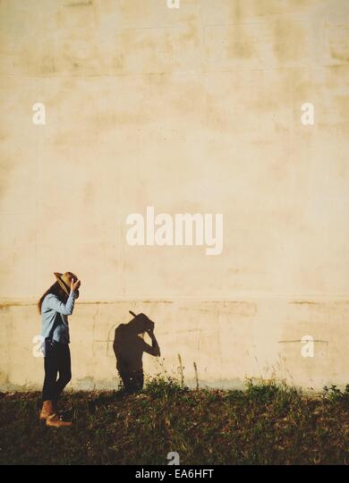 Girl in cowboy hat looking at shadow - Stock Image