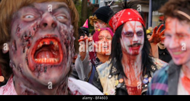 Blurred mob of bloody Zombies attacking bystander victims while having fun lurching along in the annual Toronto - Stock Image