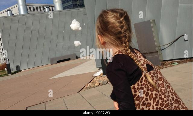 Little girl throws snowball. - Stock Image