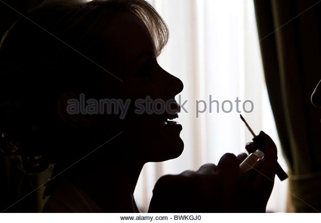 Woman putting on make up - Stock Image