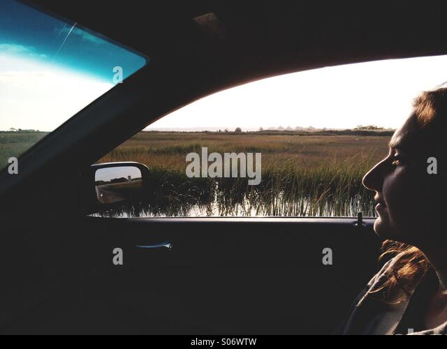 A young woman in the passenger seat of a car during a trip through rural Connecticut, USA . - Stock Image