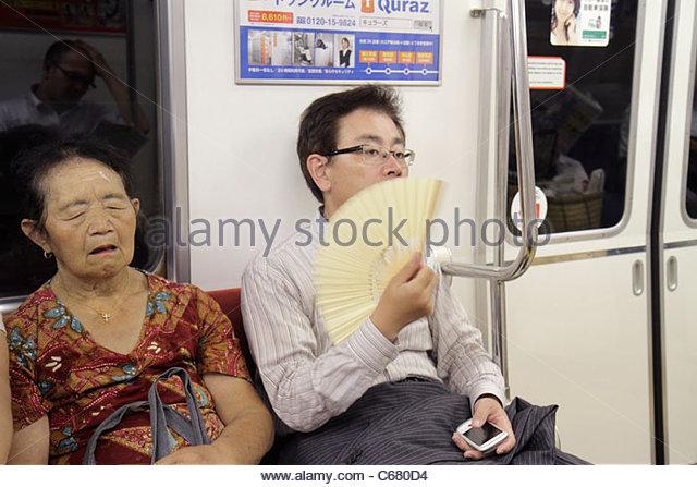 Tokyo Japan Tsukiji Oedo Line Tsukishima Station train subway car Asian man woman senior nodding off dozing asleep - Stock Image