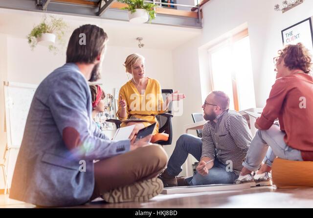 Design professionals meeting sitting on floor - Stock-Bilder