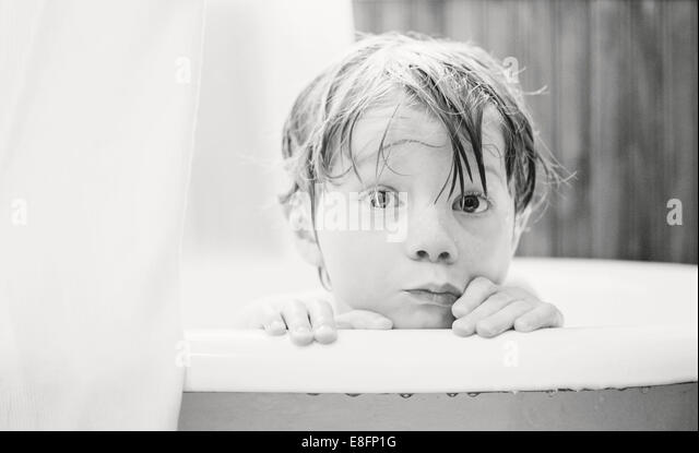 Boy  (4-5) looking over edge of bathtub - Stock Image
