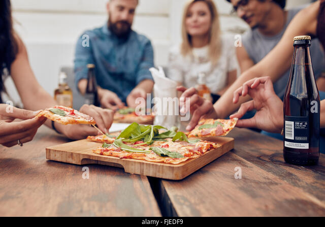 Close up shot of pizza on table, with group of young people sitting around and picking up a portion. Friends partying - Stock Image