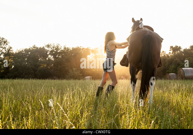 Woman walking horse in meadow - Stock Image